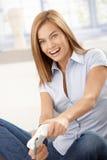 Giovane femmina che gioca sorridere del video gioco Fotografia Stock