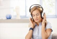 Giovane femmina che gode degli occhi di musica chiusi immagine stock