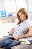 Giovane femmina che impara nel paese seduta in poltrona Fotografie Stock
