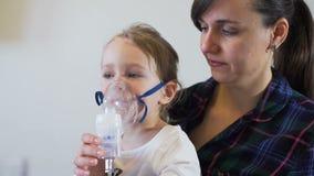 Giovane femmina che inala sua figlia con il nebulizzatore archivi video