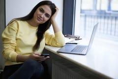 Giovane femmina che si siede vicino alla finestra in caffetteria piacevole con i dispositivi digitali e che usando wifi 4G Fotografie Stock Libere da Diritti