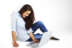 Giovane femmina che si trova giù e che per mezzo del computer portatile Immagini Stock Libere da Diritti