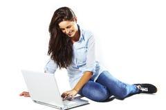 Giovane femmina che si trova giù e che per mezzo del computer portatile Immagine Stock