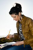 Giovane femmina che studia all'aperto Fotografie Stock