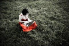 Giovane femmina che utilizza un computer portatile nella natura immagine stock