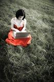 Giovane femmina che utilizza un computer portatile nella natura fotografia stock