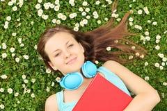 Giovane femmina con il libro e le cuffie che si trovano su un'erba con flusso Immagini Stock Libere da Diritti