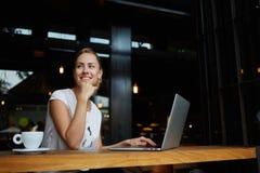 Giovane femmina con il sorriso sveglio che si siede con il NET-libro portatile nell'interno moderno della caffetteria durante il  Immagini Stock