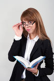 Giovane femmina con un libro ed i vetri Fotografia Stock Libera da Diritti