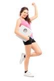 Giovane femmina felice che tiene una scala del peso Immagini Stock