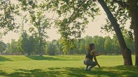 Giovane femmina flessibile attraente che fa elemento acrobatico nel parco alla mattina di estate, movimento lento stock footage