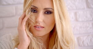 Giovane femmina sensuale che tocca i suoi capelli biondi lunghi archivi video