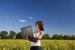 Giovane femmina sul campo di frumento con il computer portatile Immagine Stock