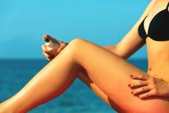 Giovane femminile bello, applicando la crema di abbronzatura Fotografie Stock