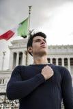 Giovane fiero davanti alla bandiera italiana con l'espressione sicura Fotografie Stock Libere da Diritti