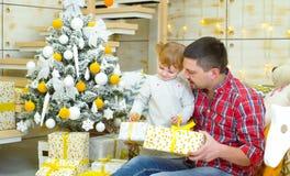 Giovane figlia del bambino e del padre che si siede vicino all'albero di Natale ed ai contenitori di regalo d'apertura immagini stock