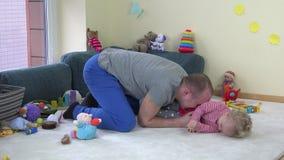 Giovane figlia felice del bambino di solletico del padre su tappeto fra i giocattoli a casa video d archivio