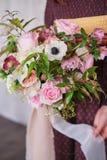 Giovane fiorista femminile che tiene un mazzo floreale di fioritura appena fatto dei garofani rosa pastelli e dell'eucalyptus con immagini stock