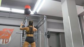 Giovane forte donna con l'ente perfetto di forma fisica in abiti sportivi che si esercita con la palla medica alla palestra Ragaz stock footage
