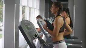Giovane forte donna con l'ente perfetto di forma fisica nel funzionamento degli abiti sportivi sulla pedana mobile in palestra Ra Immagini Stock Libere da Diritti