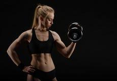 Giovane forte donna muscolare esile che posa nello studio con la testa di legno Immagine Stock Libera da Diritti