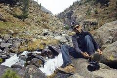 Giovane fotografo che fa un'escursione, sedentesi sulla roccia e legante le sue scarpe Immagini Stock Libere da Diritti