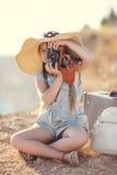 Giovane fotografo con un grande cappello su una roccia Fotografia Stock Libera da Diritti