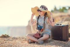 Giovane fotografo con un grande cappello su una roccia Immagini Stock