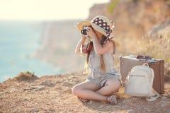 Giovane fotografo con un grande cappello su una roccia Fotografia Stock