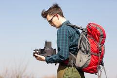 Giovane fotografo con uno zaino e una macchina fotografica d'annata alla ricerca dei posti pittoreschi fotografia stock libera da diritti