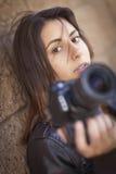 Giovane fotografo Holding Camera della femmina adulta della corsa mista Immagine Stock