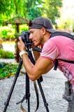 Giovane fotografo maschio che fotografa natura nel parco su un bl fotografia stock
