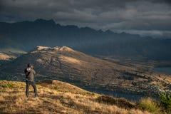Giovane fotografo maschio che prende foto di paesaggio a Queenstown Immagini Stock Libere da Diritti