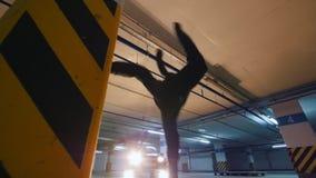 Giovane freerunner alla moda del tipo che fa una vibrazione dalla parete nel garage, elementi acrobatici del parkour, movimento l archivi video