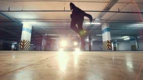 Giovane freerunner alla moda del tipo che fa una vibrazione dalla parete nel garage, elementi acrobatici del parkour, movimento l video d archivio