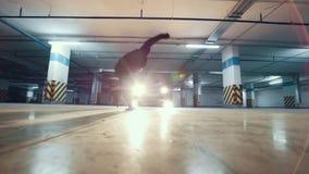 Giovane freerunner alla moda dell'uomo che esegue un verticale, elementi acrobatici del parkour, movimento lento video d archivio
