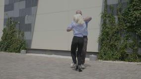 Giovane frestyle abile del latino di dancing delle coppie di affari all'aperto vicino ad un centro di affari che si rilassa e che stock footage