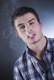 Giovane fumo caucasico bello dell'uomo Fotografie Stock Libere da Diritti