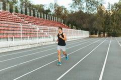 Giovane funzionamento atletico dell'uomo sullo stadio di mattina Immagine Stock Libera da Diritti