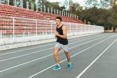 Giovane funzionamento atletico dell'uomo sullo stadio di mattina Immagini Stock