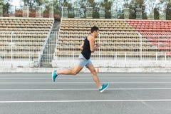 Giovane funzionamento atletico dell'uomo sullo stadio di mattina Fotografia Stock Libera da Diritti
