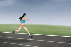Giovane funzionamento atletico della donna Fotografia Stock