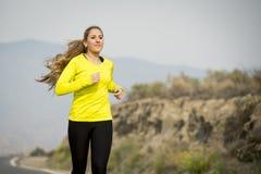Giovane funzionamento attraente della donna di sport sulla strada asfaltata con il fondo del paesaggio della montagna del deserto Immagini Stock