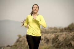Giovane funzionamento attraente della donna di sport sulla strada asfaltata con il fondo del paesaggio della montagna del deserto Fotografia Stock