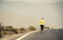 Giovane funzionamento attraente della donna di sport sulla strada asfaltata con il fondo del paesaggio della montagna del deserto Fotografie Stock