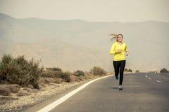 Giovane funzionamento attraente della donna di sport sulla strada asfaltata con il fondo del paesaggio della montagna del deserto Fotografia Stock Libera da Diritti