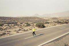 Giovane funzionamento attraente della donna di sport sulla strada asfaltata della montagna del deserto Immagini Stock Libere da Diritti