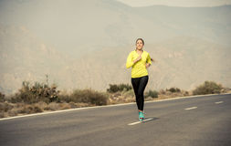 Giovane funzionamento attraente della donna di sport sulla strada asfaltata della montagna del deserto Immagine Stock Libera da Diritti