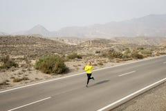 Giovane funzionamento attraente della donna di sport sulla strada asfaltata della montagna del deserto Immagini Stock