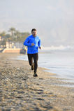 Giovane funzionamento dell'uomo di sport nell'allenamento di forma fisica sulla spiaggia lungo il primo mattino del mare Immagini Stock